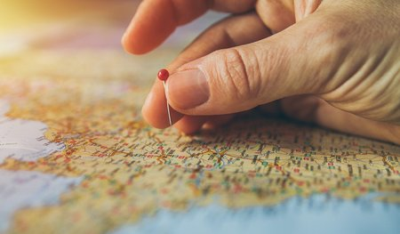 A hand holding a pin, hovering above a map (Image by piviso from Pixabey)