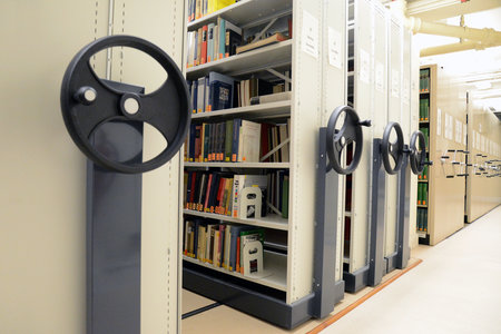 Movable library shelving units with books, the wheels to move the roller racking can be seen in the foreground