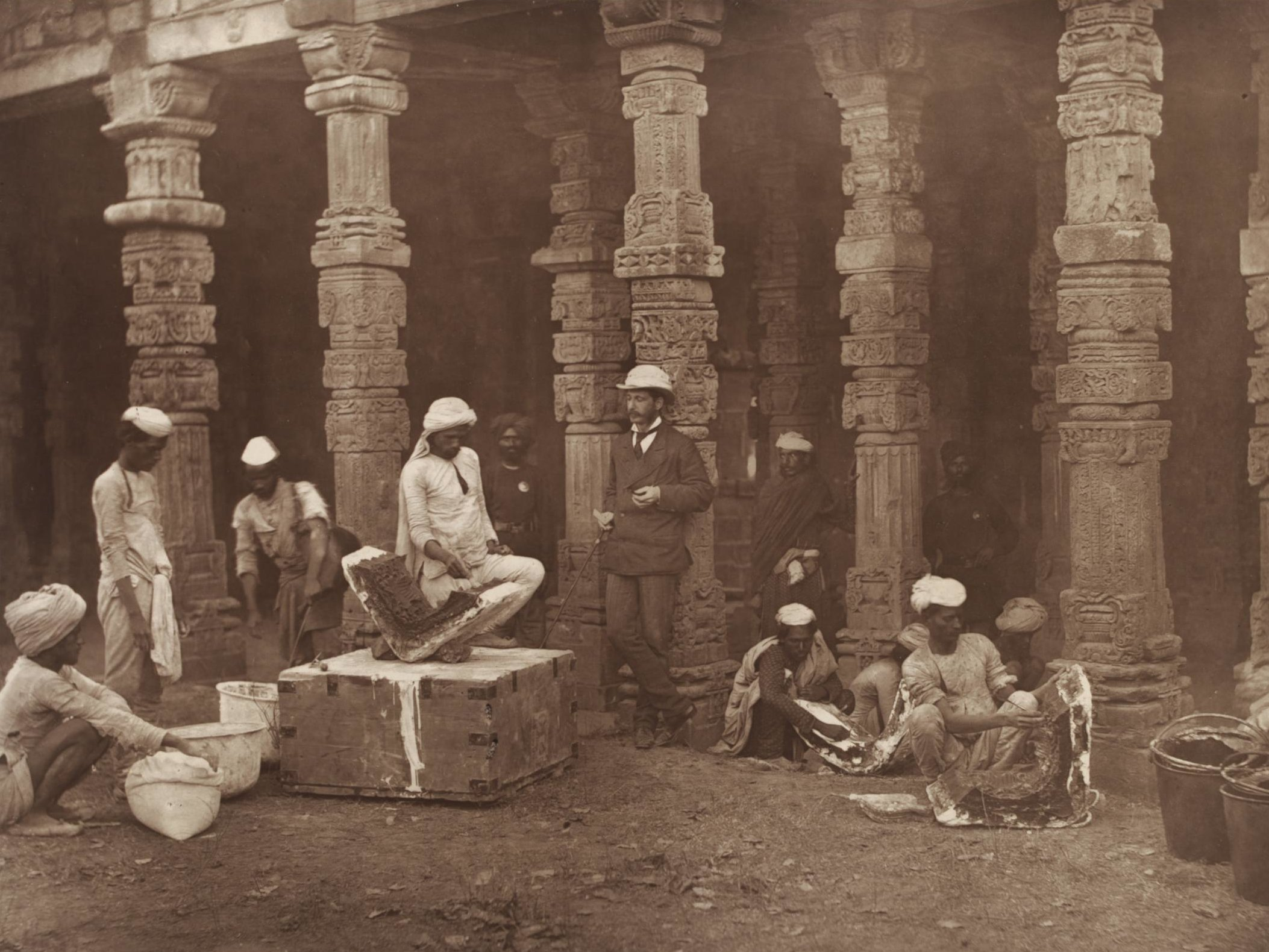 Indian moulders, supervised by a colonial official, at work. Qutb Minar, Delhi, 1856