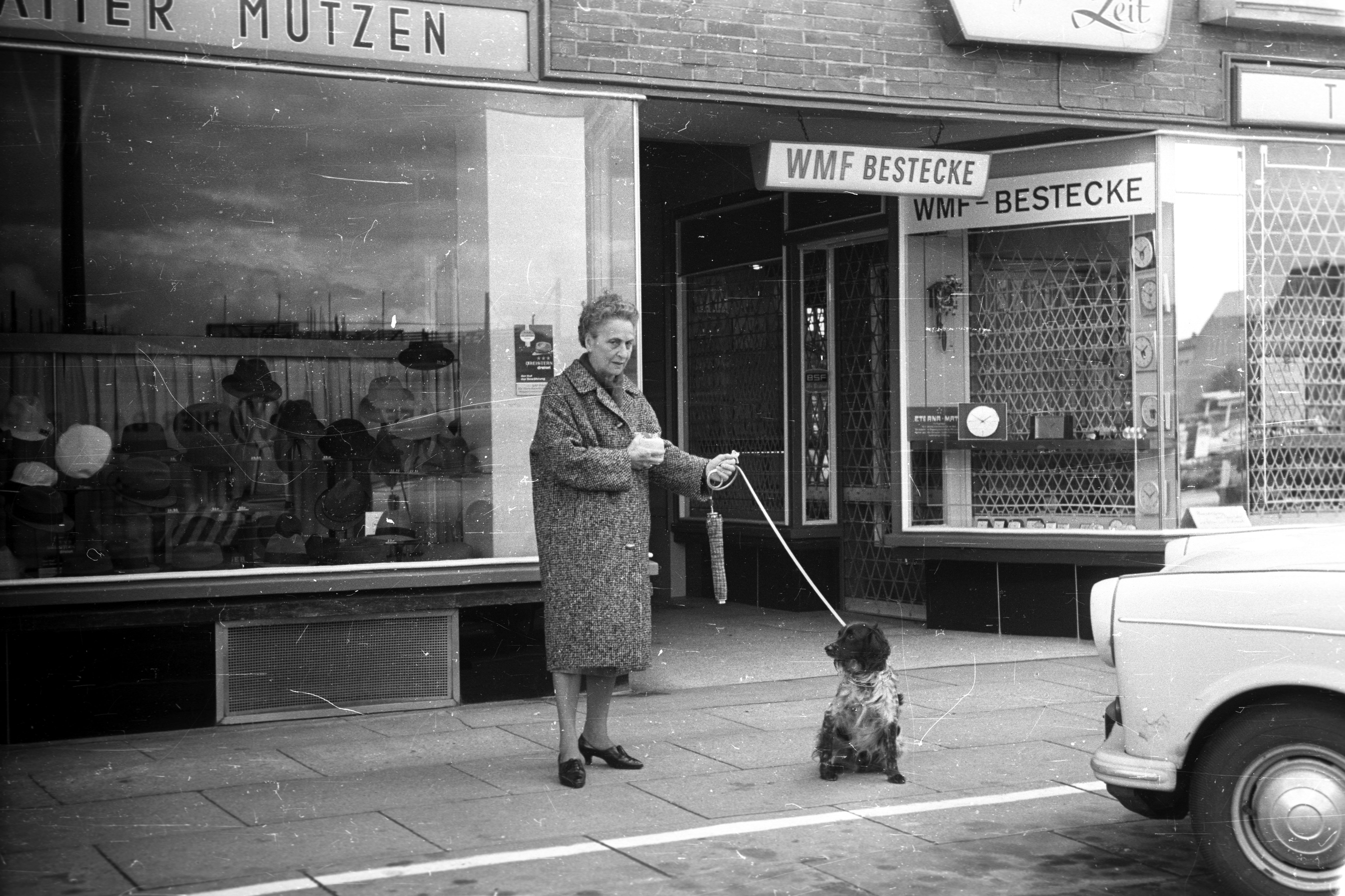 A black and white image of an older lady with her spaniel, in front of a rank of shops on Hamburger Strasse in Hamburg, 1965, featuring cutlery and men's hats