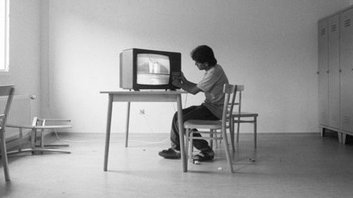 Black and white photograph of Asylum seeker in Gauting (Bavaria, Germany) watching television. By Andreas Bohnenstengel [CC BY-SA 3.0 de]