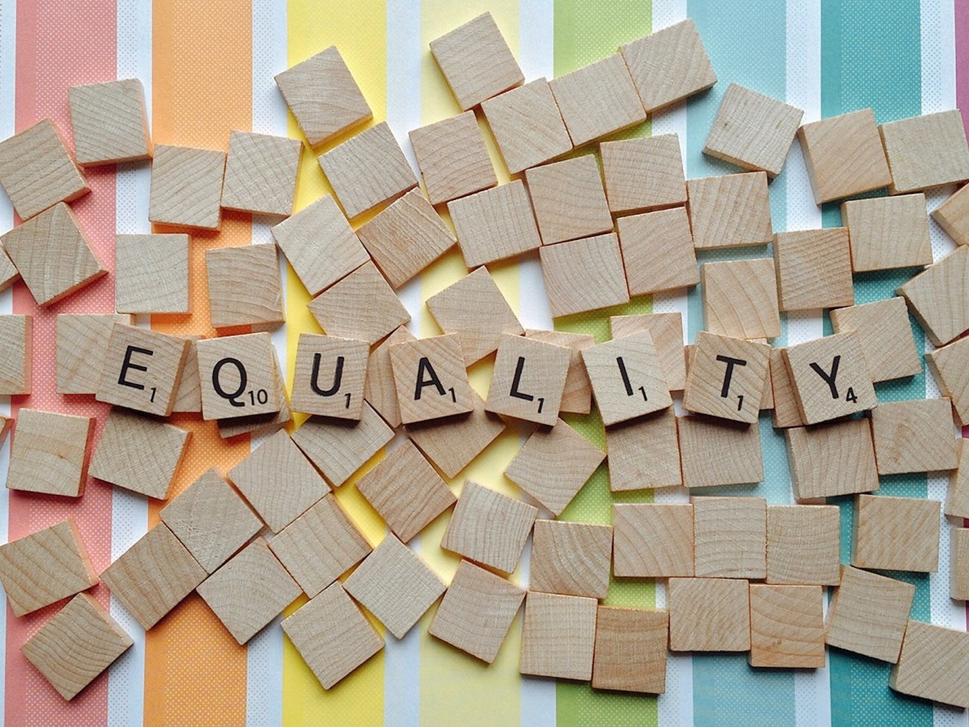 Scrabble tiles spelling out the word 'equality', on a pile on blank tiles on top of a rainbow stripe background