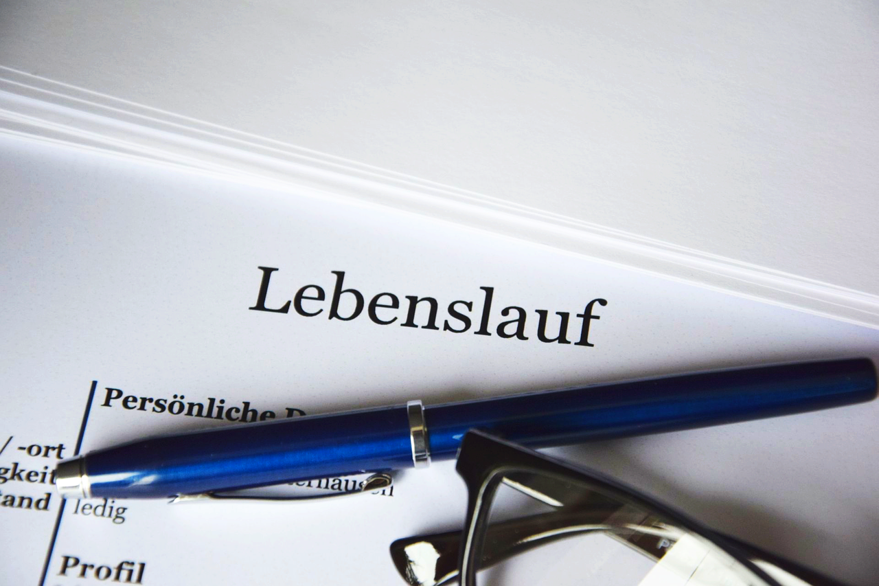 A pen and a pair of glasses on top of a CV entitled Lebenslauf